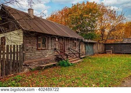 Autumn Village Landscape. Old Wooden Village House On The Background Of Autumn Stormy Sky Under The