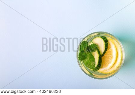 Sassy Water For Detox Infused With Lemon, Cucumber And Mint In Glass On Light Blue Background. Top V