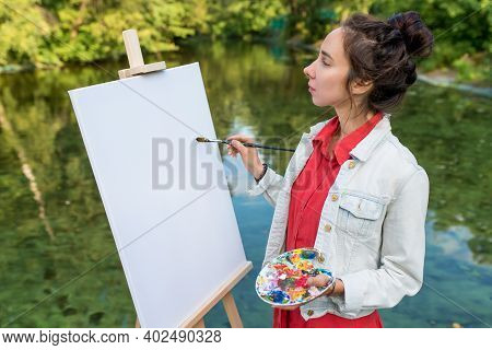 Woman Artist In Summer In Park Near Lake, River Pond, Draws Picture, White Canvas, Start Drawing. Cr