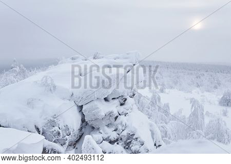 Winter View From Rocky Mountain Ridge To The Snowy Wooded Hills In Frosty Haze