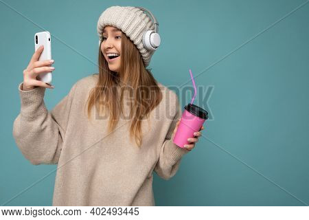 Attractive Overjoyed Delightful Young Blonde Woman Wearing Beige Sweater And Beige Hat White Headpho