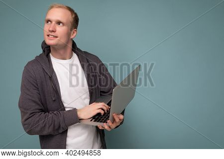 Side Profile Photo Shot Of Handsome Blonde Man Holding Computer Laptop Typing On Keyboard Having An