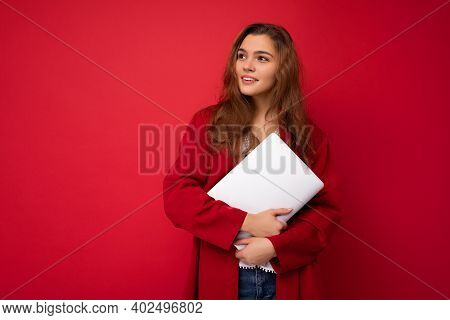 Charming Mysterious Young Curly Lady Holding Netbook Wearing Red Cardigan And White Blouse Looking T