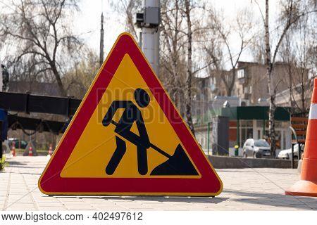 Roadworks Warning Sign Ahead On Street Sidewalk. Close-up