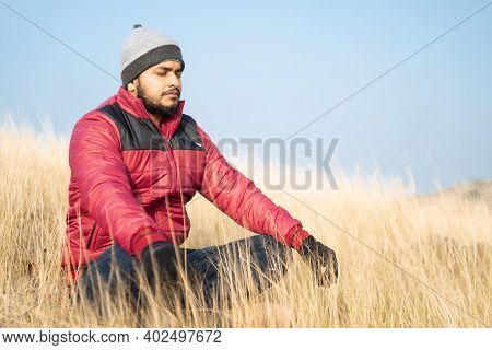 Traveller Meditating On Top Of The Mountain During Cold Morning - Concept Of Connecting With Nature,