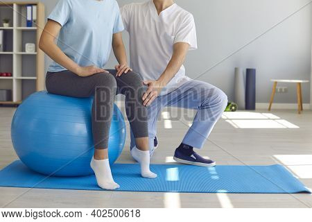 Woman Doing Exercise On Fit Ball With Professional Physiotherapist Or Chiropractor Helping Her