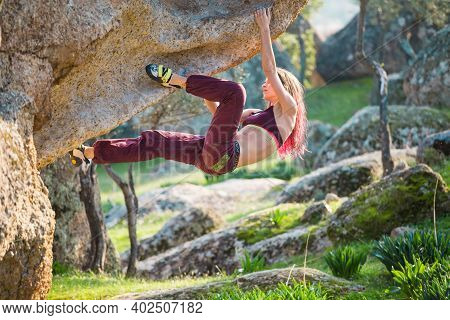 Beautiful Sports Girl Rock Climber Climbs The Overhanging Stone. Bouldering In Nature. Sport Climbin