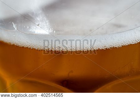 Close Up Of A Amber Beer Or Ale Foam On The Top Of A Beer Pint Glass  On A Sunny Day. Selective Focu