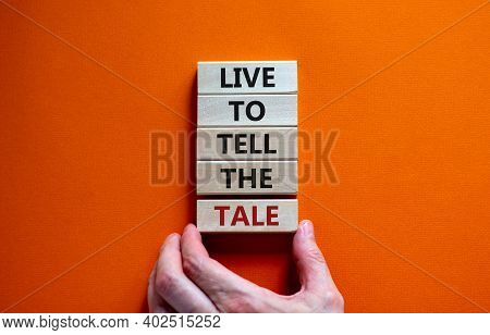 Live To Tell The Tale Symbol. Wooden Blocks With Words 'live To Tell The Tale' On Beautiful Orange B