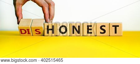 Honest Or Dishonest Symbol. Businessman Hand Turns Cubes And Changes The Word 'dishonest' To 'honest