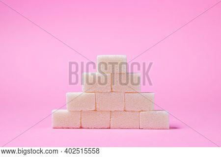 Sugar Cubes On A Pink Background. Sugar Pyramid. Refined Sugar.