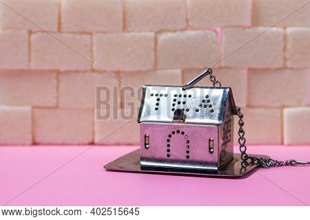 House-shaped Tea Strainer On A Pink Background. Tea Strainer With Sugar Cubes. Refined Sugar. Small