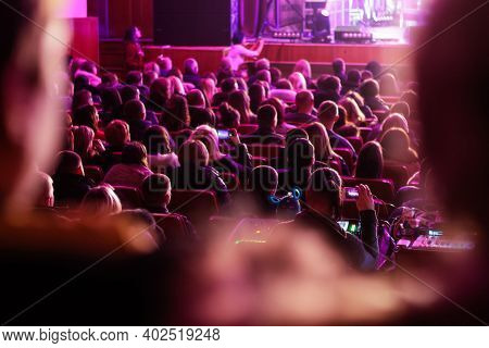 Defocused Spectators Sit In The Hall And Watch A Concert. People In The Auditorium Watching The Perf