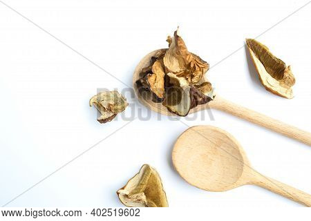 Dried Porcini Mushrooms In Wooden Spoon, Isolated, White Background