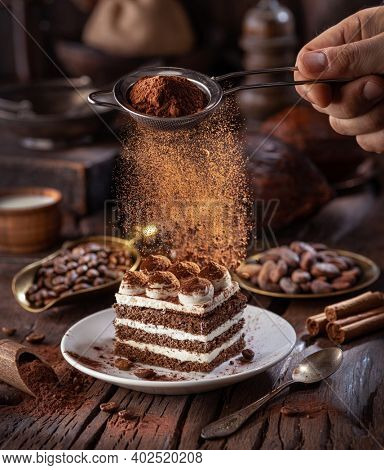 Dusting tiramisu - like cake with cocoa powder. Still life with slice of cake and coffee and cacao beans on wooden table.