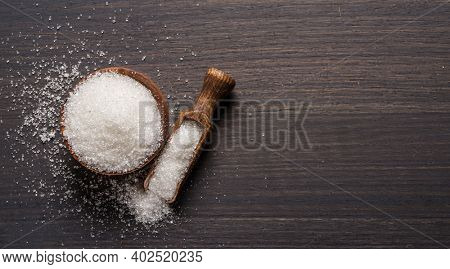 White refined sugar in wooden bowl and spoon on dark wooden table.