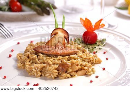 Risotto with roasted porcini mushrooms on white plate. Close-up.