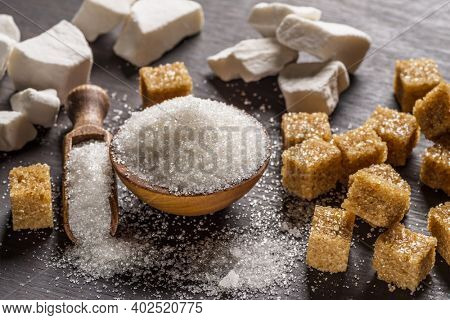 Granulated table sugar in wooden bowl and in the spoon and sugar cubes around it on the table.