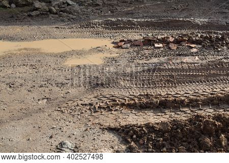 Muddy Broken Road Made Of Earth And Clay Without Asphalt With Large Muddy Puddles, Bricks, Tire Mark