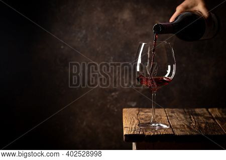 Pouring Red Wine Into The Glass Against Rustic Dark Wooden Background