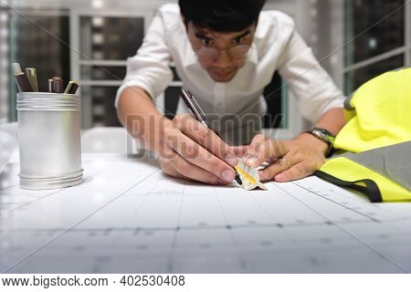Engineer Designer Sketching With Blueprint Architecture On Desk Office In-home At Night, Working Ove