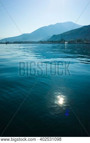 Vertical seascape, calm blue water with sunny bunny, mountains on horizon in Fethiye bay, Turkey. Shades of blue