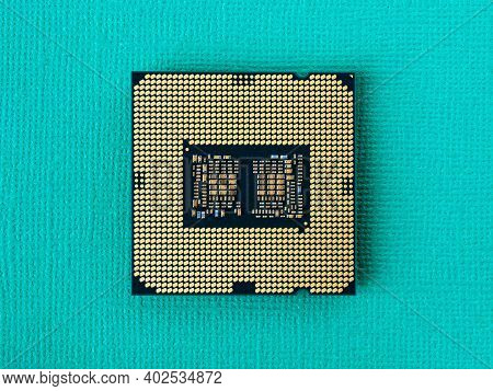 Pc Micro Cpu With Gold Plated Contacts On A Textured Turquoise Background. Modern Central Processing