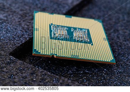 Pc Micro Cpu With Gold Plated Contacts On A Textured Dark Background. Modern Central Processing Unit