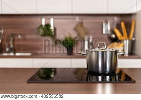 Selective Focus On Cooking Pot On Electric Stove Near Wooden Countertop Against Blurred Background W