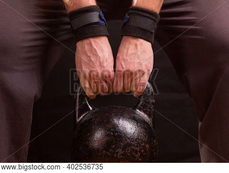 Sports Kettlebell In The Hand Of The Athlete. The Athlete Is Holding A Kettlebell.