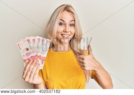 Beautiful caucasian blonde girl holding 10 colombian pesos banknotes smiling happy and positive, thumb up doing excellent and approval sign