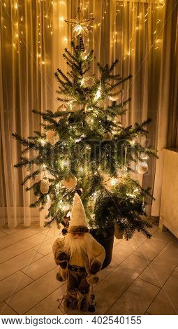 Christmas Tree With Lights And Santa Claus Figure In A Low-light Room, String Lights In The Backgrou
