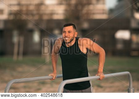 Young Fit Man Doing Triceps Dips On Parallel Bars Outdoors. Doing Exercises On Parallel Bars