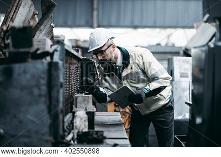Technicians Man Or Engineer Holding Tablet For Checking Work In A Heavy Industrial Factory Behind. T