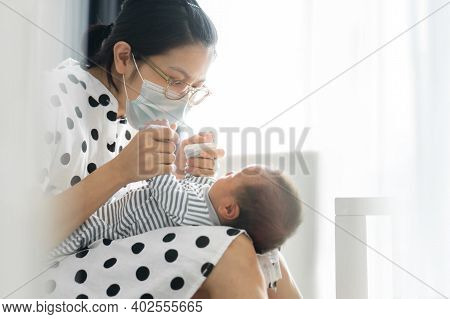 Portrait Of Beautiful Young Mom Wearing Protective Face Mask Playing With Baby Boy In Bedroom. Asian