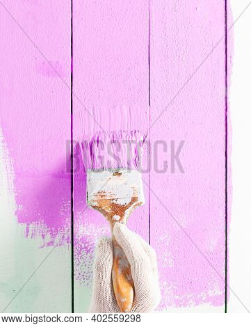 Close Up Painter Man Hand Painting Pink Color On Wooden Plank Table With Copy Space,bright Creative