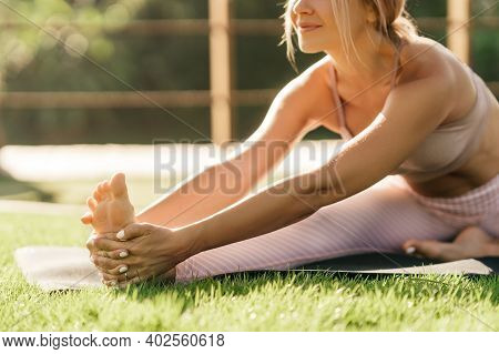 Woman Doing Stretching Exercises Outdoors In The Morning. Beautiful Happy Sport Fitness Model Outsid
