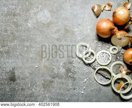 Onion Cut Into Rings On A Stone Stand. On A Stone Background.