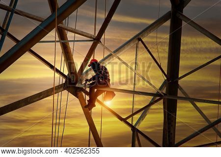 Worker Wiring Electric Power On Steel Tower,  Electric Construction And Maintenance Services Through