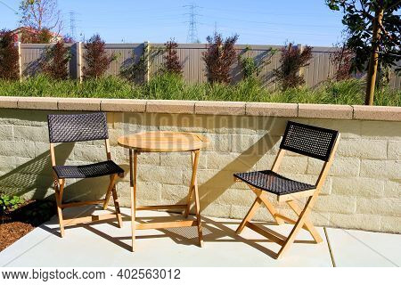 Chairs Besides A Small Wooden Table On An Outdoor Patio Taken At A Garden In A Residential Community