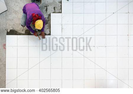 Construction Worker Tiler Is Tiling, Ceramic Tile Floor Adhesive At Factory Building.