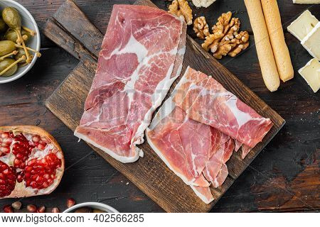 Traditional Spanish Jamon Serrano Ham Set, On Dark Wooden Background, Flat Lay