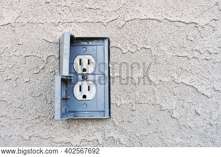 An Image Of A Grey Out Door Electrical Socket On A Grey Stucco Wall.