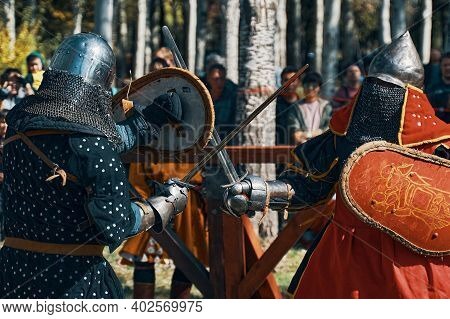 Battle Of The Red And Black Knight. Knights With Swords And Shields, In Armor. Festival Of Historica