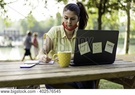 Woman Wearing Open Protective Face Mask Using Laptop Outdoors - Female Solopreneur Taking Notes Whil