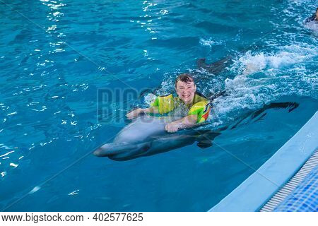 Treatment Of Children By Means Of Dolphins. Dolphin Therapy. Happy Little Girl Swimming With Dolphin