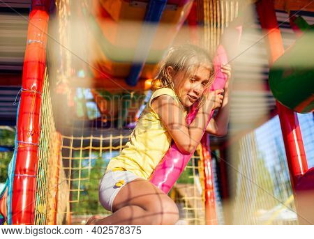 Funny Tear-stained Girl Sits On A Rug And Wipes Her Tears In An Entertainment Center With Colorful E