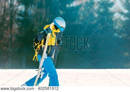 Woman Walking By Skiing Slope With Skies