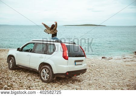 Woman Sitting On The Roof Of The Car Enjoying View Of Sea