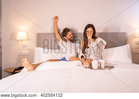 Happy Looks Of A Couple In Love In Pajamas Having Breakfast In The Hotel Bed In A Cafe, Lifestyle Of